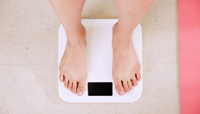 woman weights herself after incorporating CBD oil to her diet regime