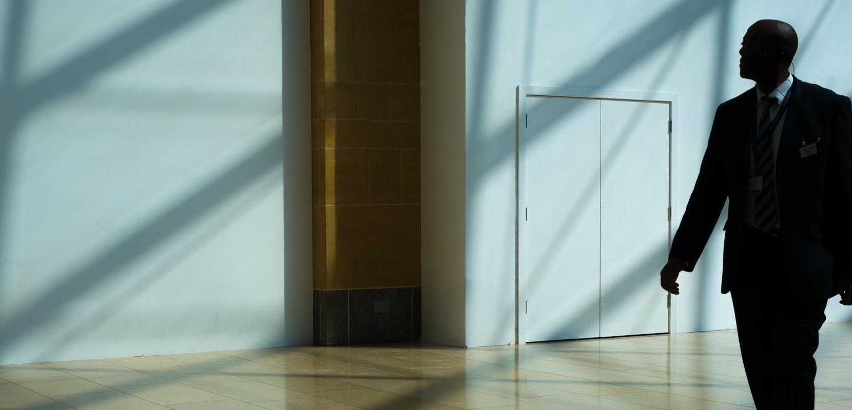 photo of man standing close to a door