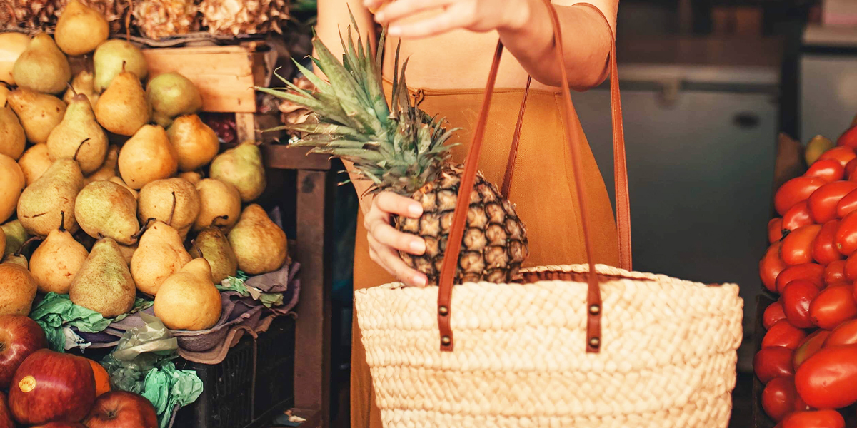 woman putting pineapple in shopping bag