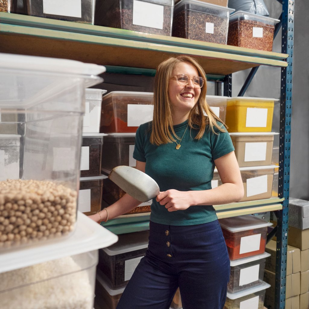 Image of Ellie in front of industrial sized shelfs stacked with boxes full of spices, grains, and pulses. She's wearing a green t-shirt and blue trousers, and is holding a grey ingredient scoop in her right hand.