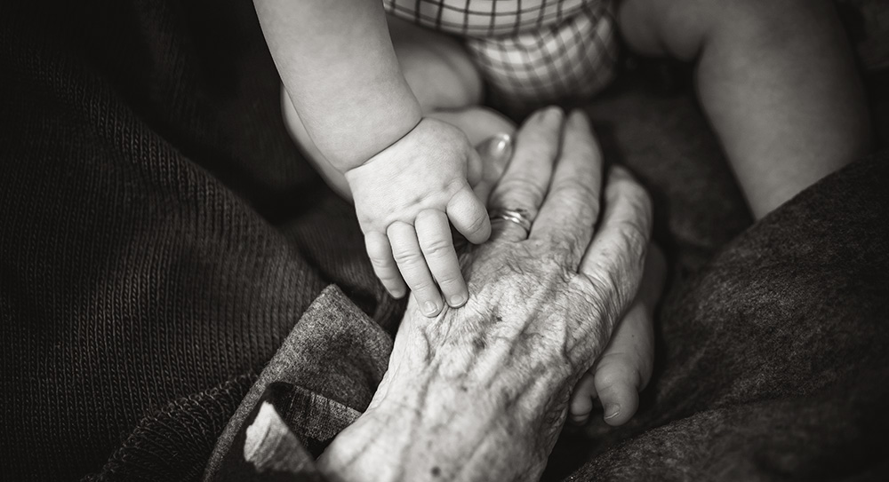 A black and white image of an baby's hand gripping the little finger of a more aged hand.