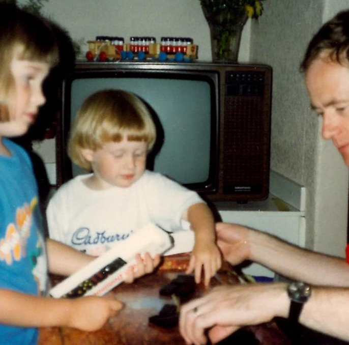 Old photo of children playing dominoes with dad, blonde one wearing cadburys tshirt