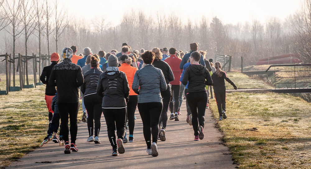 Image taken of the back of a large group of runners running along a wide path in a park. There are trees in the distance and a hazy light with lots of mist - it looks cold and frosty on the grass either side of the path.
