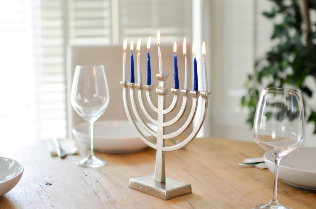 Silver menorah with blue and silver candles on a naturally-lit dinner table