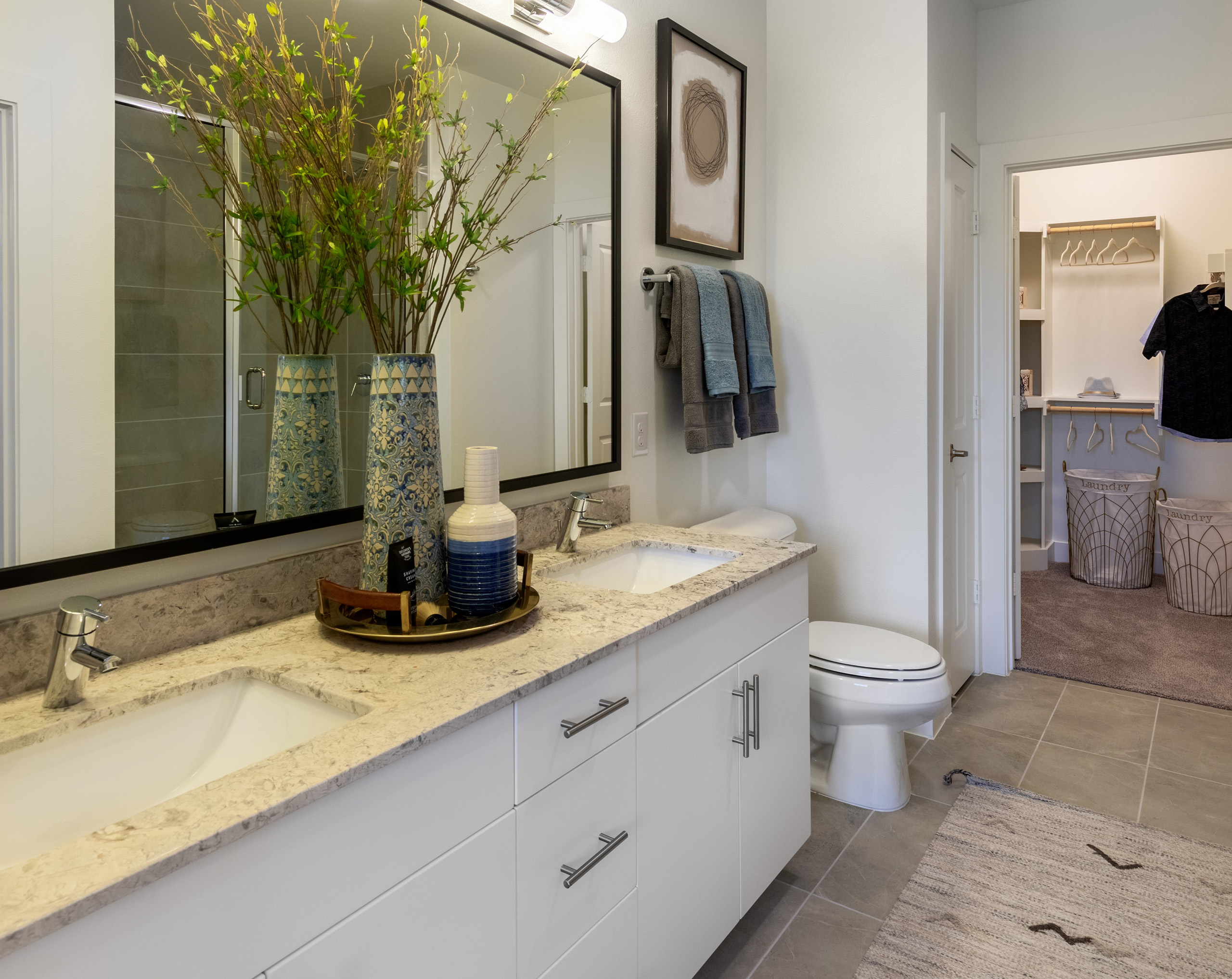 Interior view of AMLI Grapevine apartment bathroom with white granite countertops and a double vanity and a walk-in closet