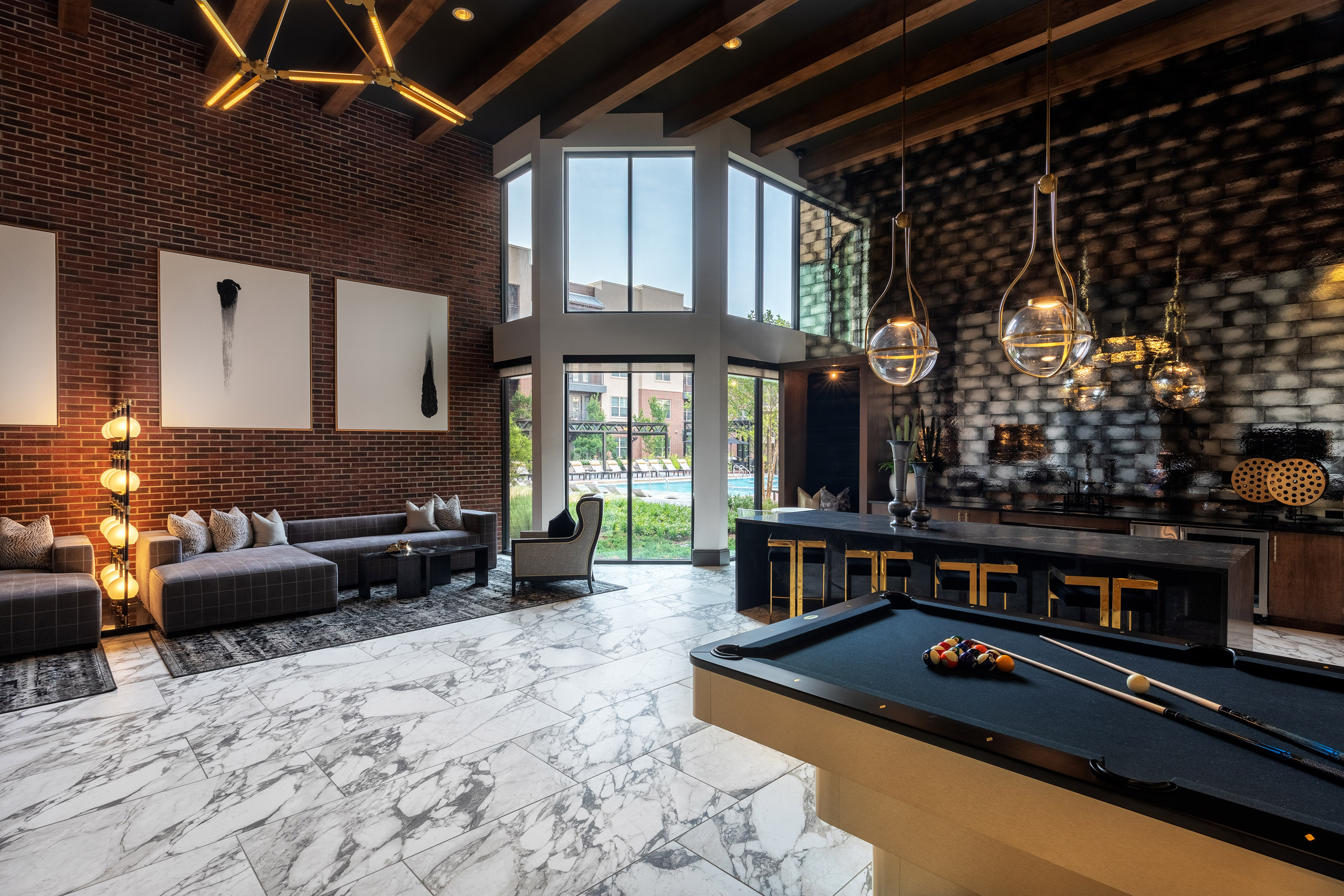 AMLI Grapevine apartment building clubroom with gray tile flooring and catering kitchen and lounge seating and pool table