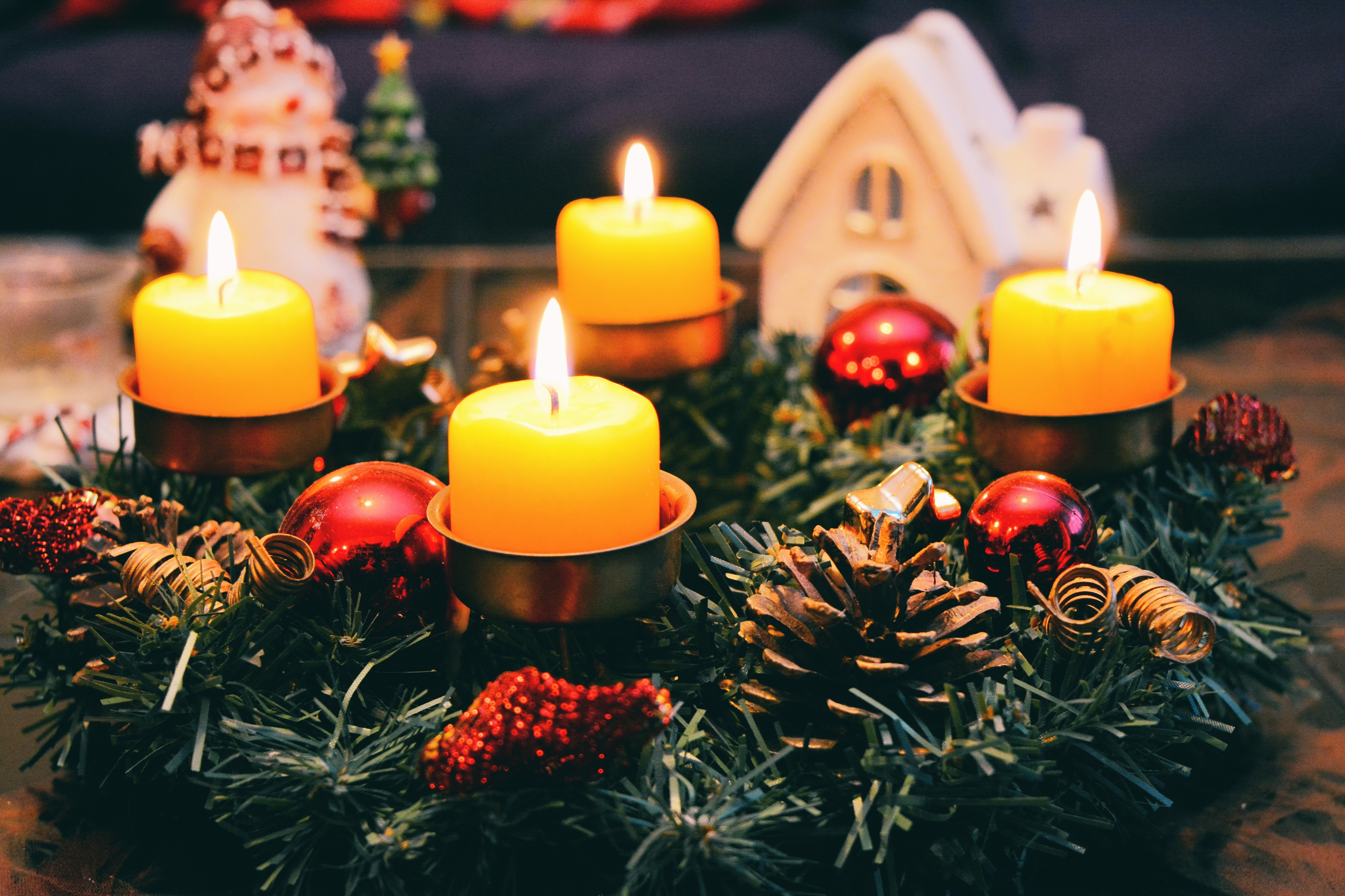 Four yellow advent candles in a green wreath on a table