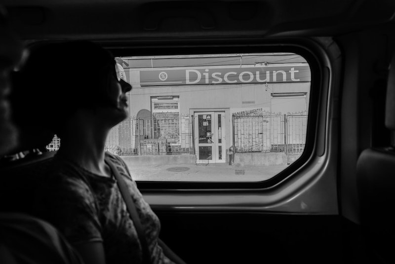 Woman in a van passing a storefront with a disount sign