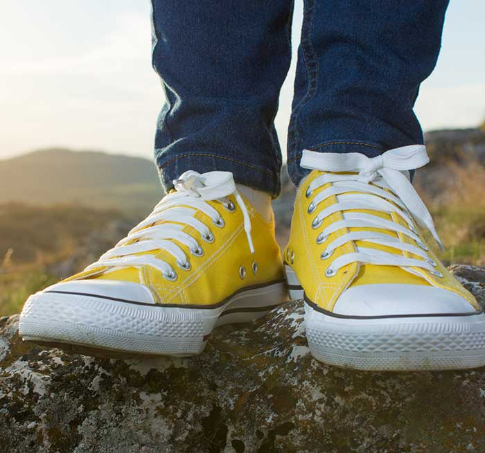 A close up image of someones shoes standing still