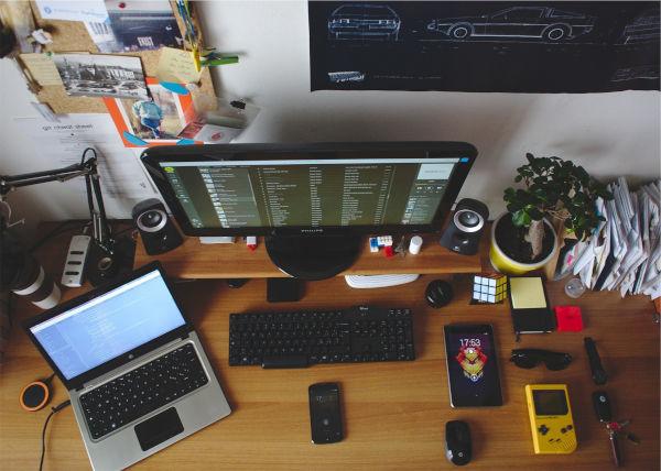 mesa com computadores e outros materiais de escritório