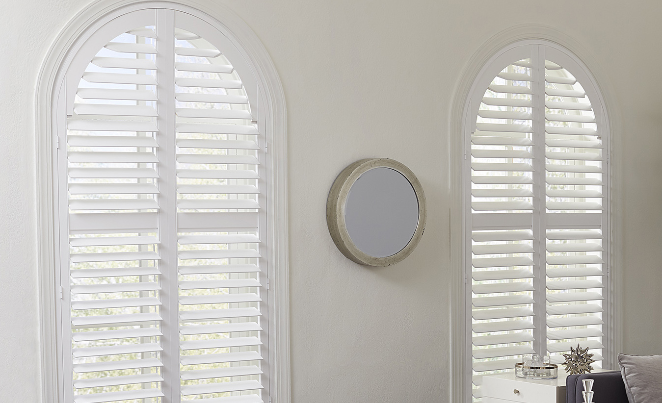 two window with arch tops covered with white plantation shutters.