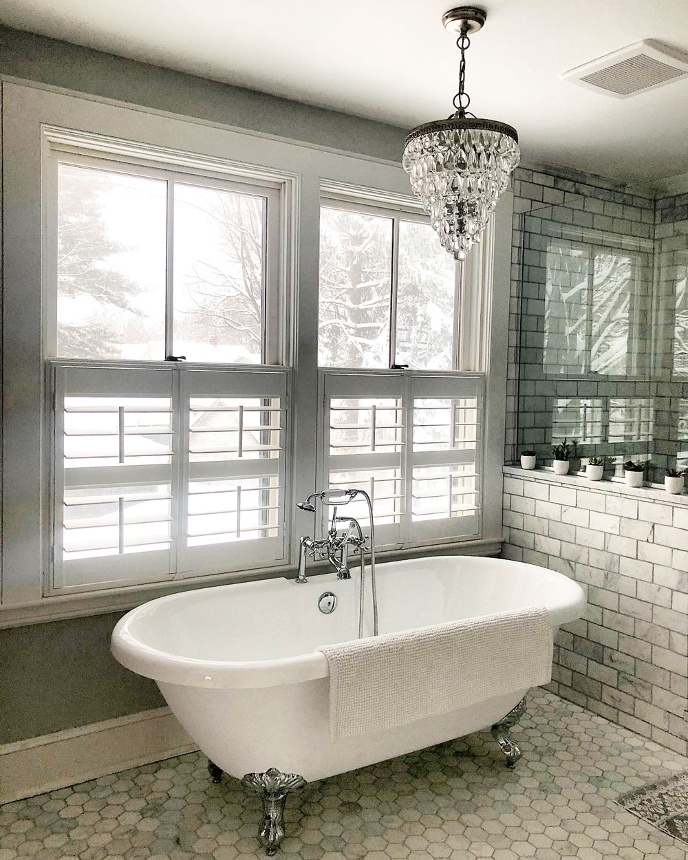 A tiled bathroom with clawfoot tub and cafe height plantation shutters in the windows.