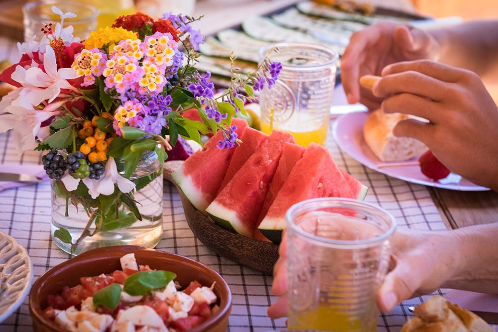 Sunny brunch table setting with watermelon, juice and flowers.
