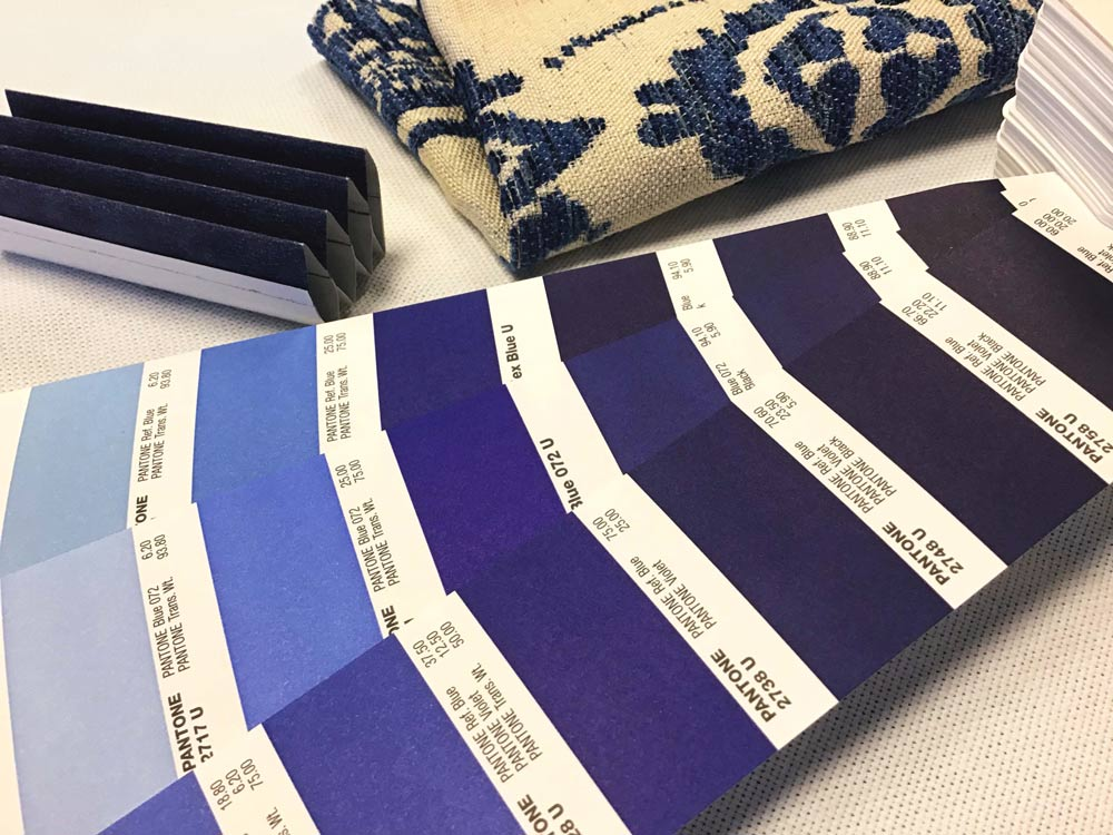 Blue Pantone swatches next to a blue cellular shade sample and a blue roman shade fabric sample.
