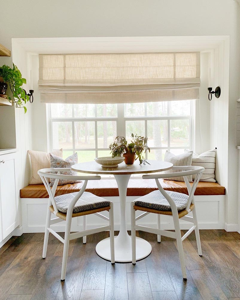 Nook dining area with cushioned bench seat and chairs. Decorated with houseplants and a beige roman shade.