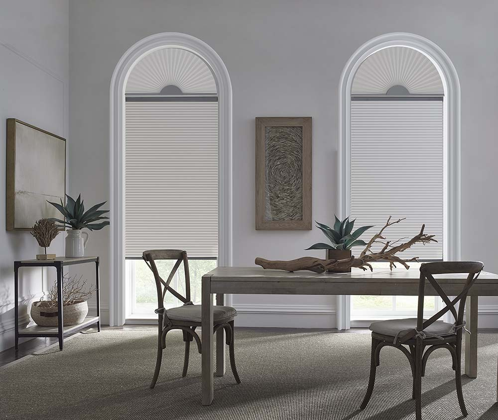 A sleek, grey dining room with tall arch top windows covered with light filtering cellular shades.
