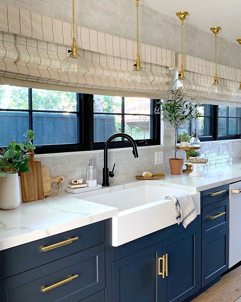 modern farmhouse kitchen with blue cabinets, white counters and brass fixtures.