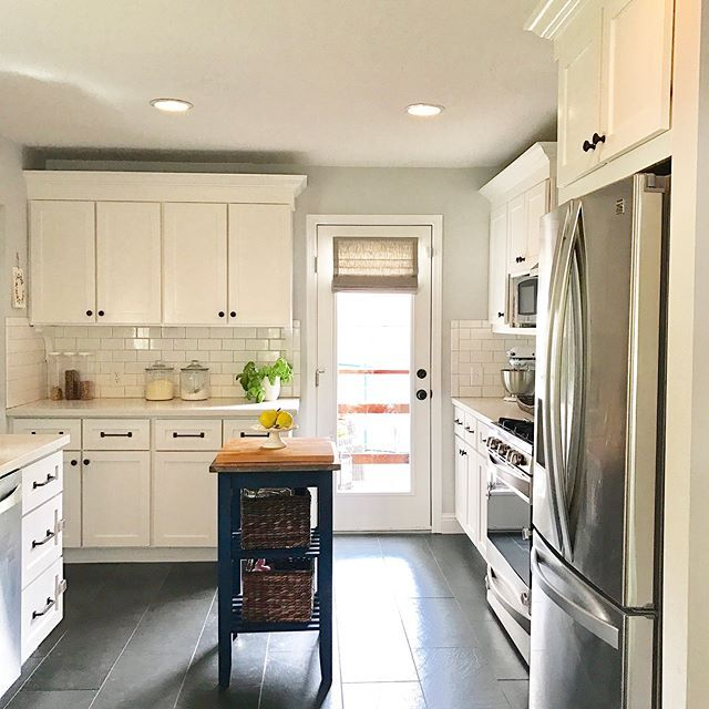 farmhouse kitchen with backdoor that has a large window in it, covered with a greige roman shade.
