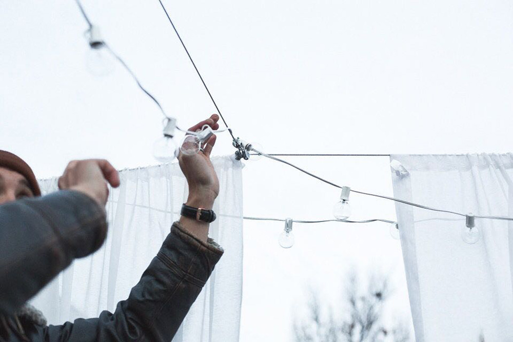 Man hanging up light strands over a patio.