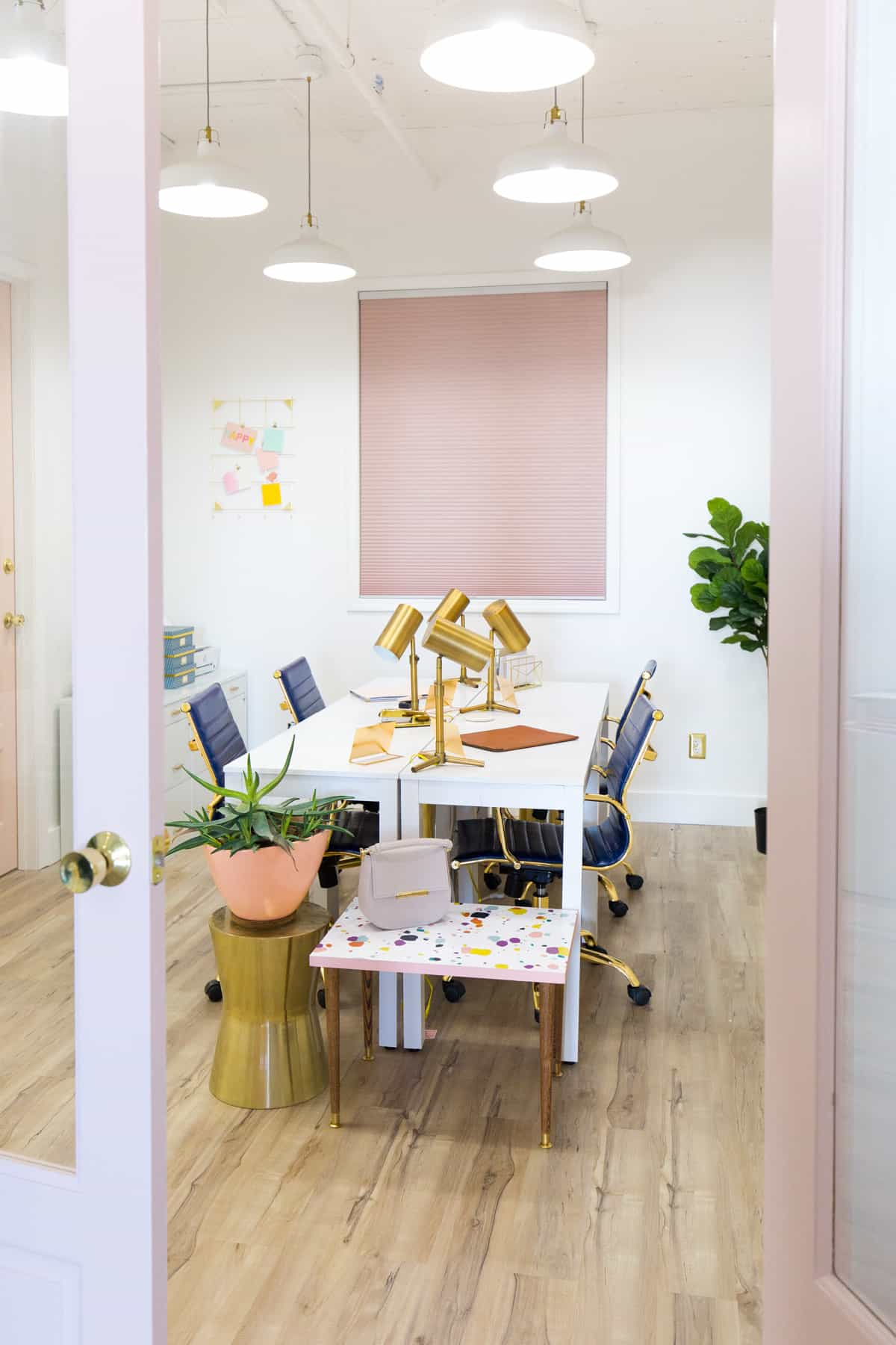 bright studio office with pink window shades and gold accents.