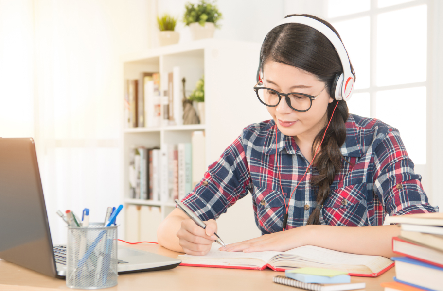 Female student writing in a notebook with headphones on