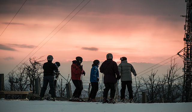 A group of skiers at the top of the ski hill