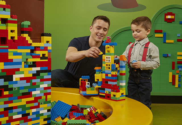 A Dad and son building a Lego Duplo tower