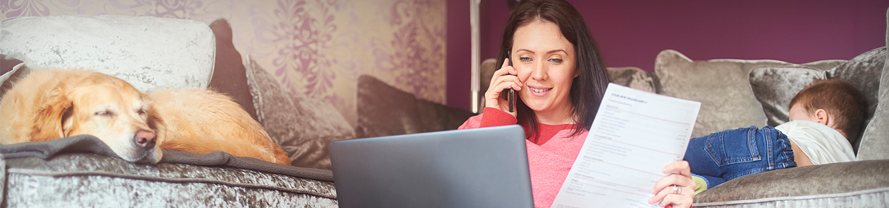 Young mother multi-tasking, working at home whilst looking after her toddler