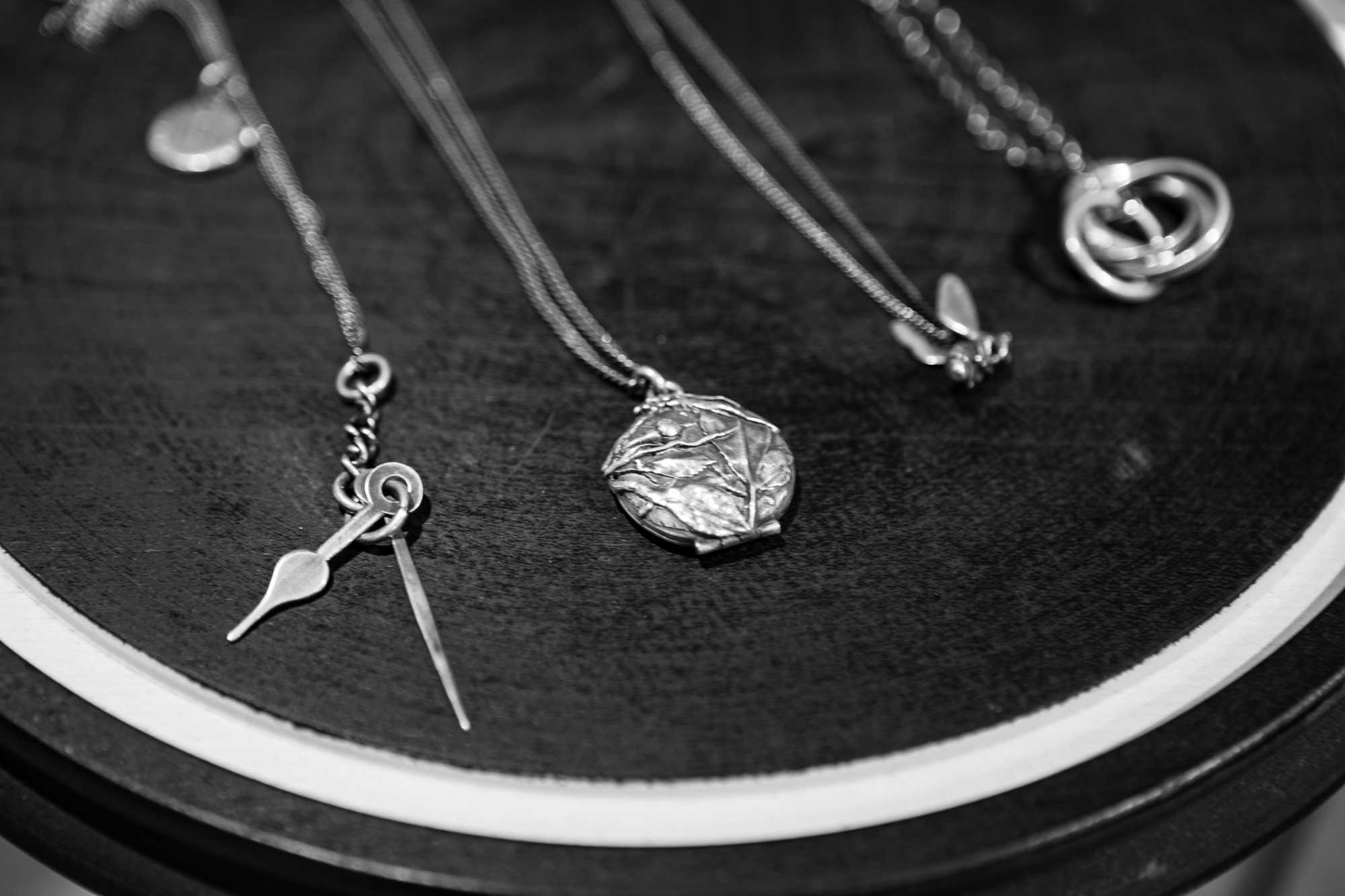 WERKSTATT:MÜNCHEN SHOWROOMMedallion Rose Bud Necklace Fine Chain Bee Necklace and Four Rings Necklace on Display FW20