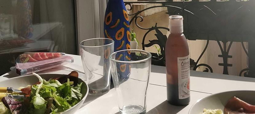 Une table avec des assiettes dessus face à une fenêtre et au soleil