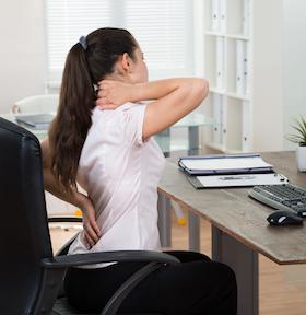Bei Getsurance ist eine Versicherung auch mit Vorerkrankungen möglich - Frau sitzt mit Schmerzen am Schreibtisch