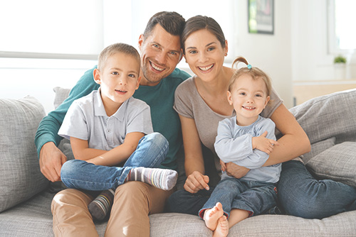 Getsurance Life - Familie mit zwei Kindern sitzt auf Sofa