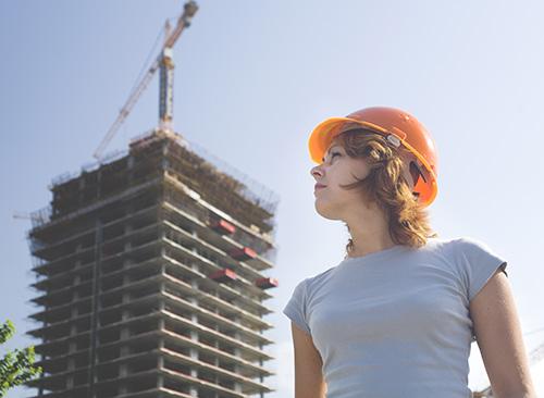 Getsurance Job - Frau mit Helm steht auf Baustelle