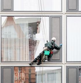 Getsurance bietet eine Versicherung auch mit Risikoberuf - Fensterreiniger hängt an Seilen vor Fassade