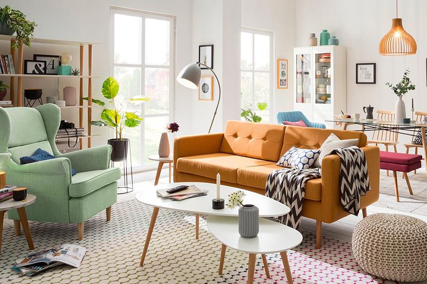 Orangenes Sofa separiert den Wohnbereich mit Sessel und Beistelltisch vom Essbereich mit Geschirrschrank und Esstisch