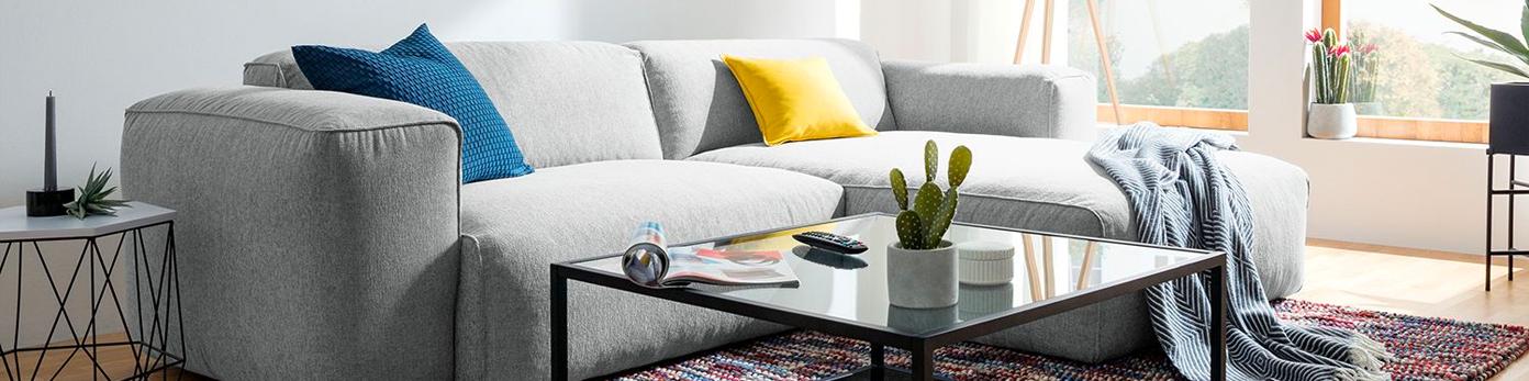 Graues Sofa mit drappierten Kissen und Decke, daneben zwei Beistelltische, auf denen Deko und Mgazine liegen