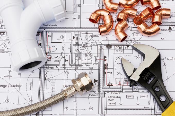 Outils de plomberie, tuyaux et plan.