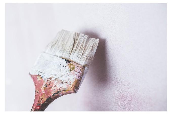 Pinceau peignant un mur en blanc.