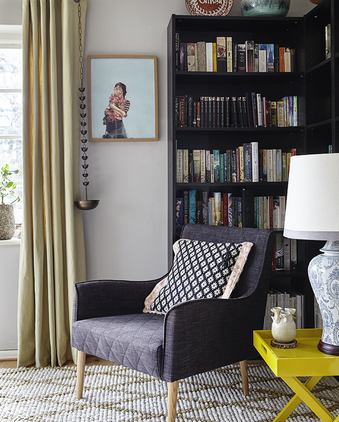 A comfy armchair in front of wall-to-wall bookshelves.