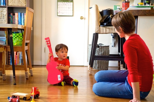 A child holding a red guitar