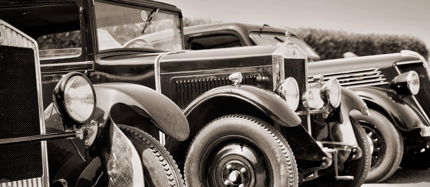 Photographie en noir et blanc présentant un ensemble de voiture de collection des années 1920.