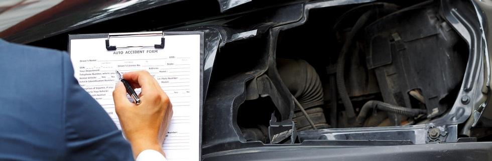 Photographie montrant un agent d'assurance constatant les dégâts sur un véhicule