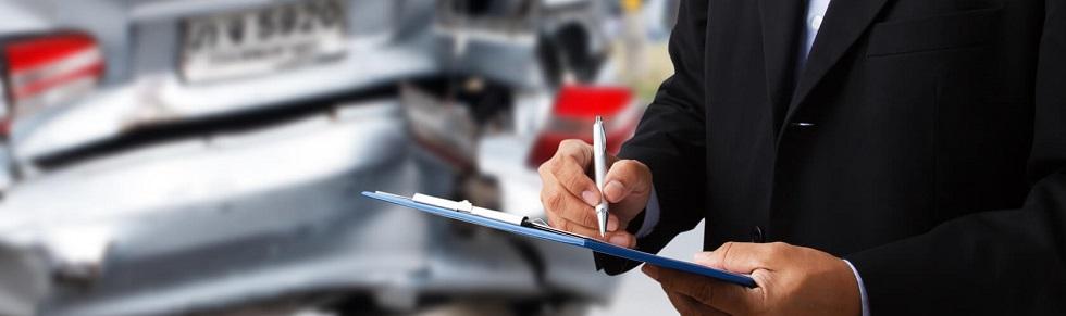 Agent des assurances inspectant l'état d'une voiture suite à un accident