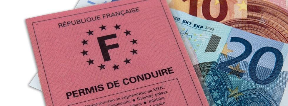 Photographie d'un permis de conduire posé sur des billets de 10 € et de 20 €