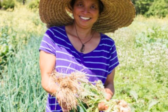 Jody of Jody's Farms holding a bushel of onions