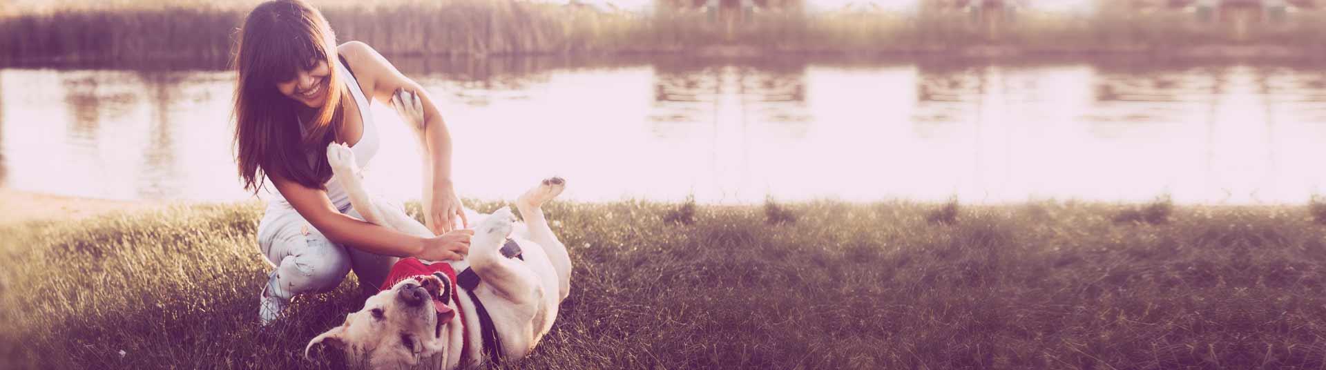 pet-sitter-jouant-avec-son-chien-au-bord-de-l-eau