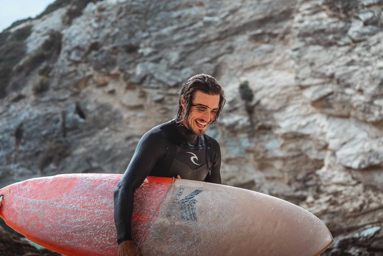 Surfeur portant une combinaison, une planche de surf à la main.