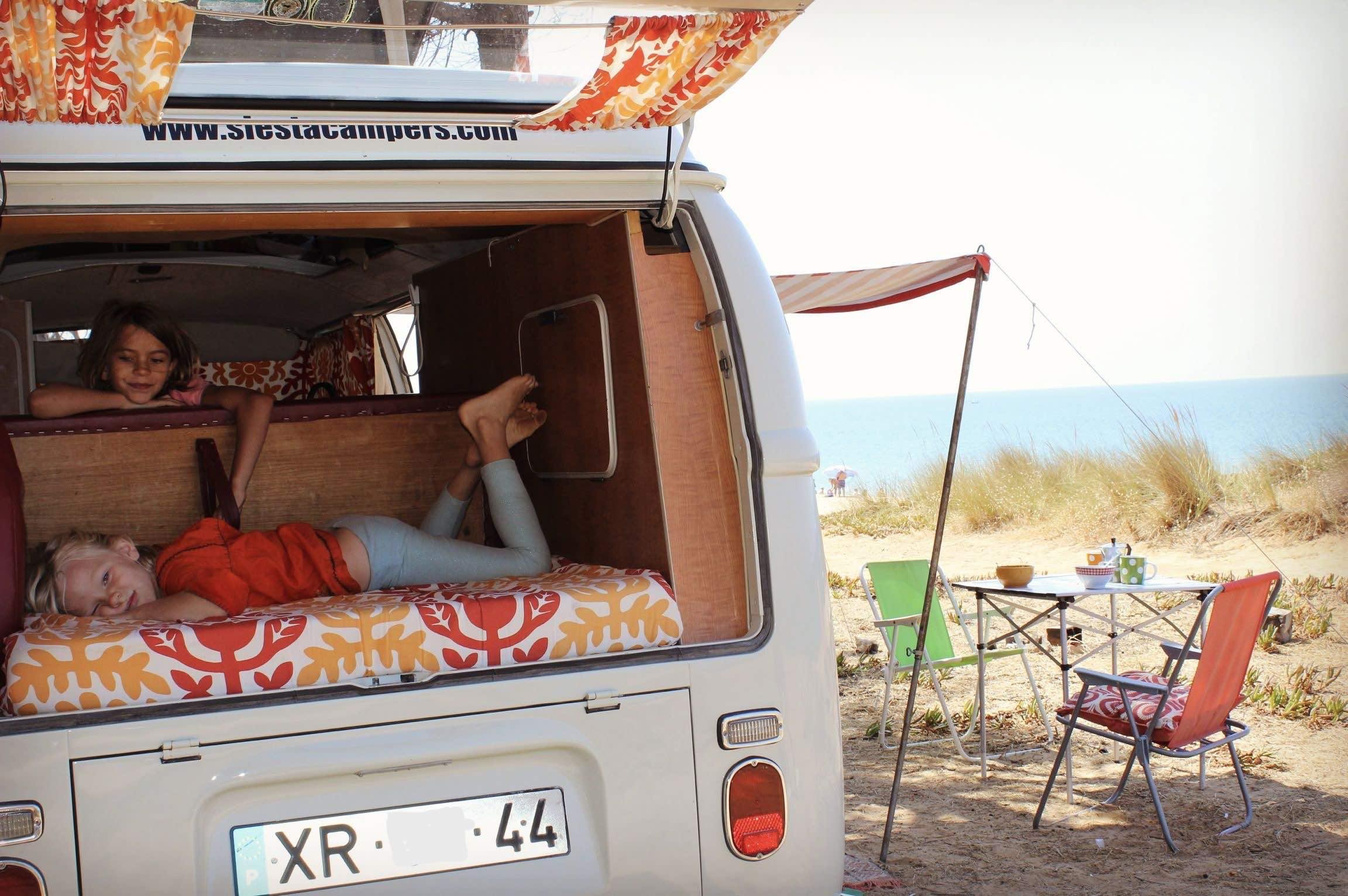 Niños disfrutando de un ritmo lento de vida en una furgoneta antigua.