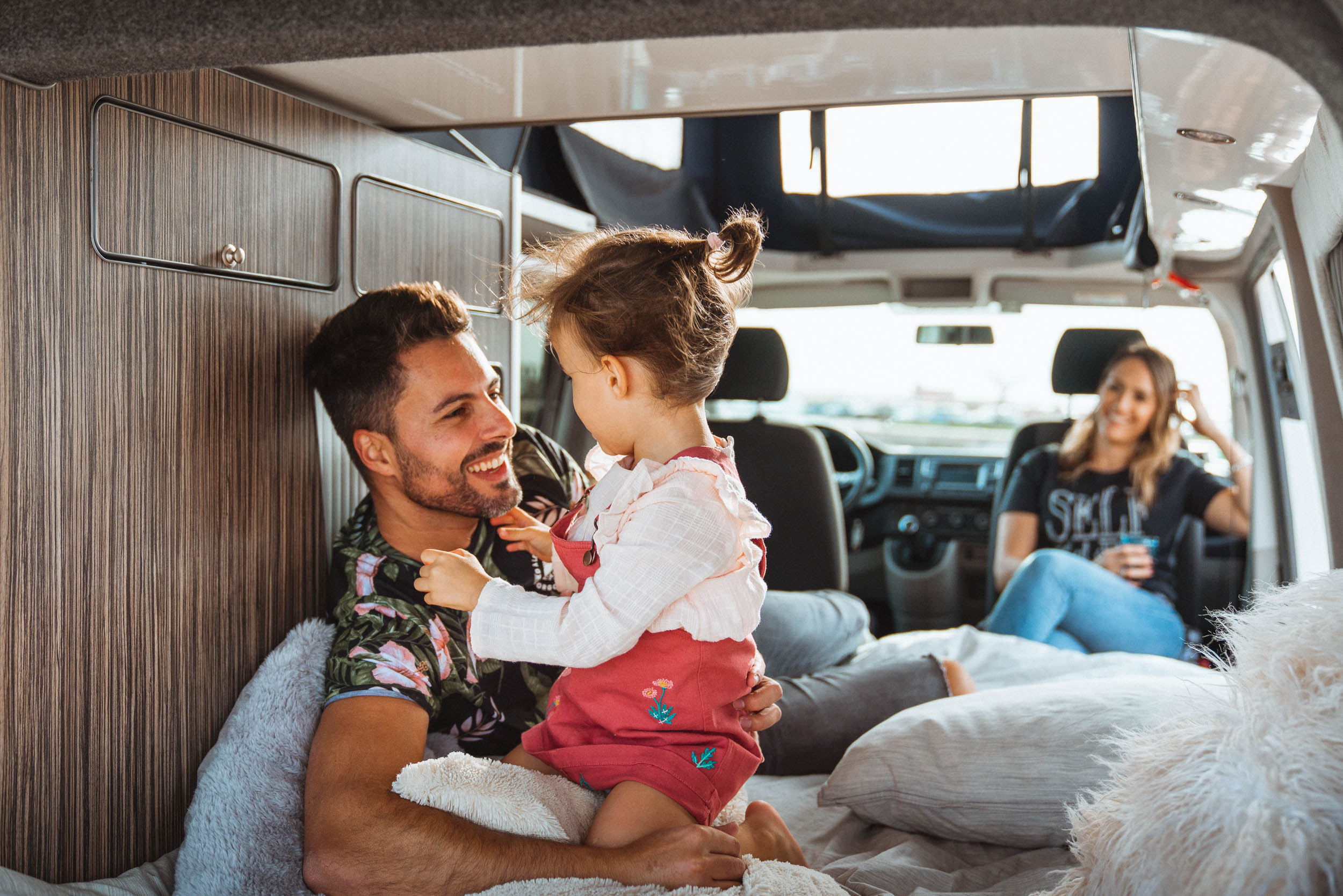 Eltem mit einem kleinen Kind, das im Inneren des Siesta Campers VW T6 Campers spielt.