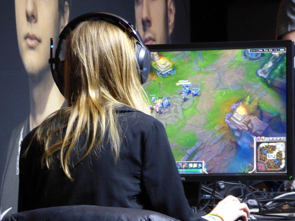 Frau sitzt vor Monitor und spielt